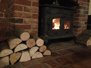 ALL FIRED UP logs stacked next to a wood burner
